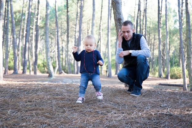 Vaterfamilie, die zusammen im park im freien spielt