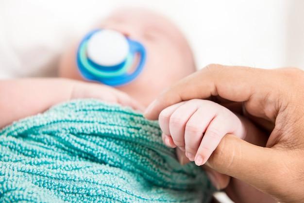 Vaterhand, die kleine babyfinger berührt und hält