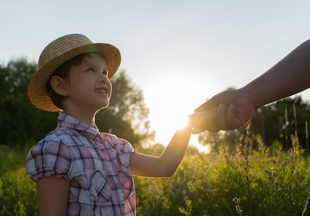 Vaters hand hält die hand eines kleinen mädchens in einem strohhut im sommer lächelt das mädchen die einstellung