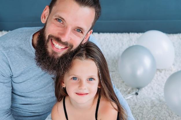 Vaterschaft. vater-tochter-bindung. liebesausdruck und glückliche familienbeziehung. porträt des lächelnden freudigen vaters, der sein kleines prinzessinnenmädchen umarmt.