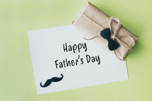 Vatertag. geschenkpaket eingewickelt mit papier und seil mit einer dekorativen fliege auf grünem hintergrund