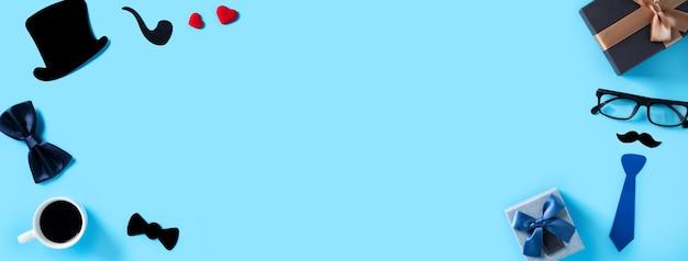 Vatertag hintergrund-design-konzept. draufsicht auf farbpapierdekorations-layout-ideen mit geschenkbox auf blauem tischhintergrund mit kopienraum.
