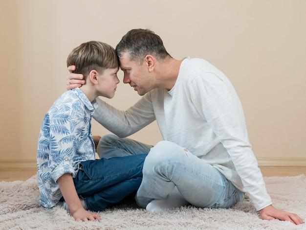 Vatertag vater und sohn berühren ihre köpfe