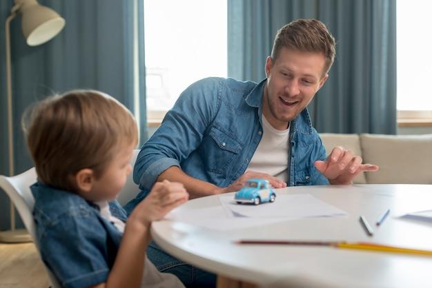 Vatertag vater und sohn spielen mit einem autospielzeug