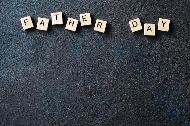 Vatertags-konzept. holzbuchstaben auf dunklem hintergrund.