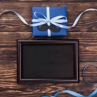 Vatertagsgeschenk mit bändern und schwarzem leerem rahmen