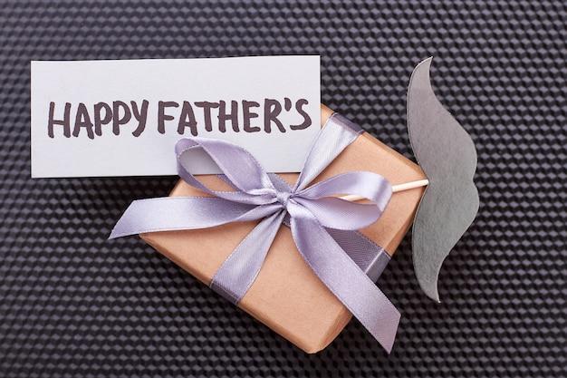 Vatertagskarte auf geschenk. schnurrbart, geschenkbox, schwarzer hintergrund. vater wird glücklich sein.