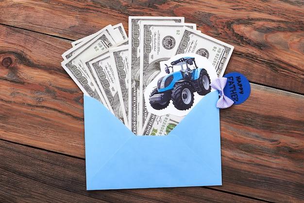 Vatertagskarte und geld. papiertraktor auf umschlag. wertschätzung des ländlichen erbes.