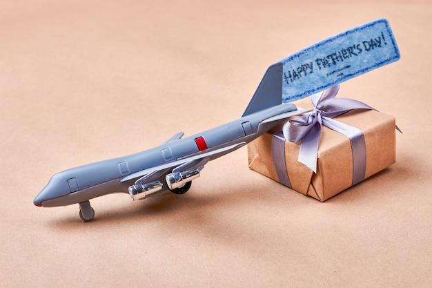Vatertagskarte und geschenk. spielzeugflugzeug in der nähe der geschenkbox. nettes geschenk im kindlichen stil.