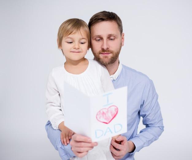 Vatertagskonzept - kleines mädchen, das ihrem vater handgemachte grußkarte auf weißem hintergrund gibt