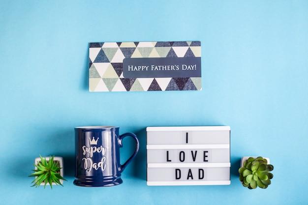 Vatertagslayout mit einem geschenkbecher, einer karte und der aufschrift i love dad