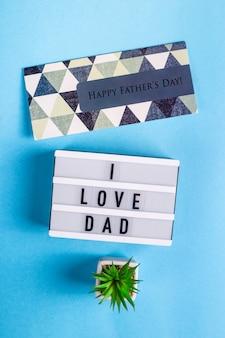 Vatertagslayout mit einer postkarte und der aufschrift ich liebe papa auf einer dekorativen lampe