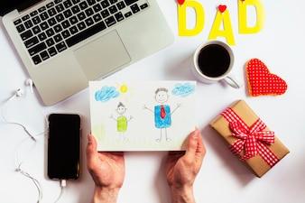 Vatertagszusammensetzung mit dem Laptop und Händen, die Zeichnung halten