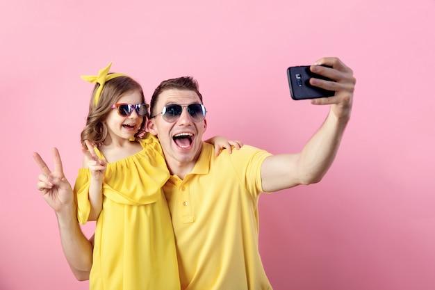 Vati und kleine tochter, die selfie mit smartphone tun