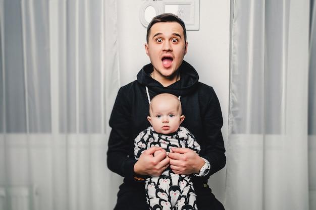 Vati und kleines baby zeigen unterschiedliche gefühle in der kamera