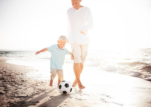 Vati und sohn, die fußball am strand spielen