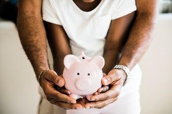 Vati und Tochter, die Sparschwein auf Händen halten