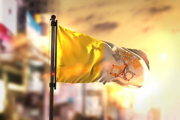 Vatikanstadt-flagge gegen stadt verschwommener hintergrund bei sonnenaufgang-hintergrundbeleuchtung