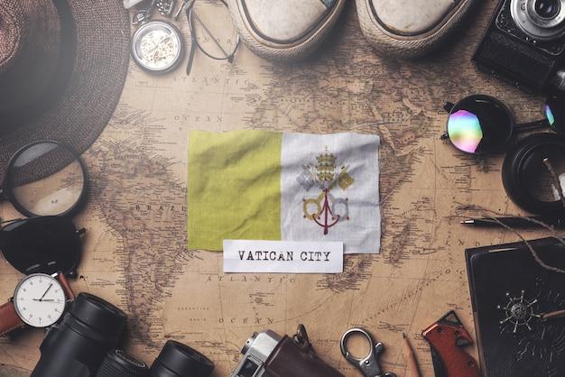 Vatikanstadt-flagge zwischen dem zubehör des reisenden auf alter weinlese-karte. obenliegender schuss