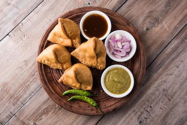 Veg samosa - ist ein knuspriger und würziger indischer tea time snack in dreiecksform, serviert mit gebratenem grünem chili, zwiebeln & chutney oder ketchup