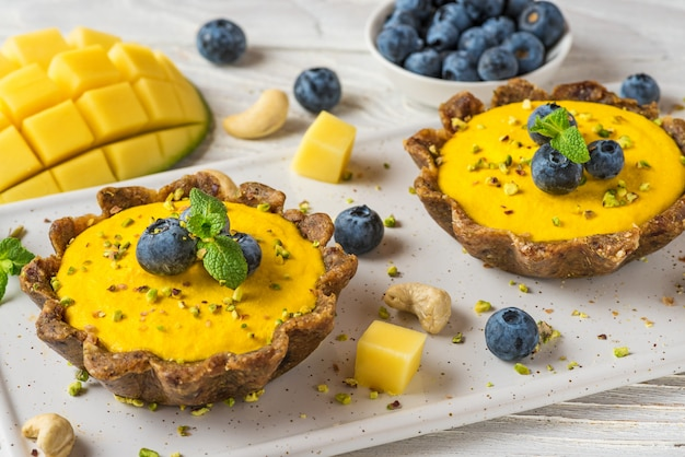 Vegan food dessert. rohe vegane gelbe mangokuchen mit frischen blaubeeren und minze. gesundes leckeres glutenfreies essen