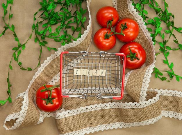 Vegan geschrieben auf holzwürfeln umgeben von gemüse in der einkaufskorb-draufsicht mit bastelpapierhintergrund, vegan, gesundes essen, vegetarisches konzept, kopierraumlebensstil