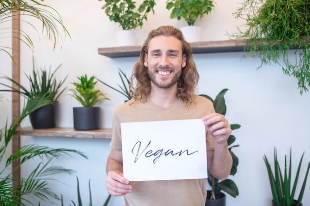 Vegan. glücklicher junger erwachsener langhaariger mann, der kleines plakat mit wort vegan vor ihm hält
