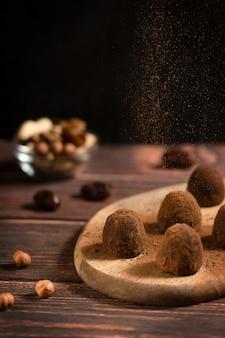 Vegane bio-schokolade-trüffel mit haselnuss- und kakaopulverstreuseln auf dunklem holztisch