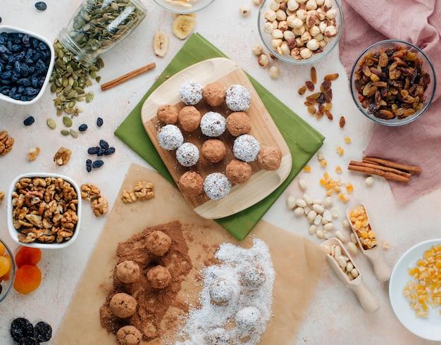 Vegane bonbons aus getrockneten früchten und nüssen mit kakaopulver und kokosnusschips überzogen