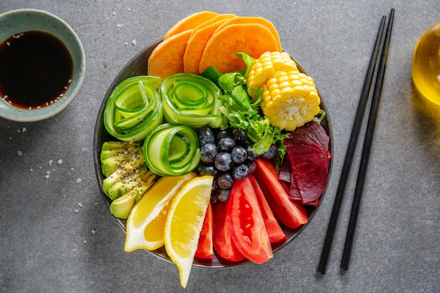 Vegane buddha-schüssel mit gemüse und früchten in schüssel auf grauem hintergrund serviert. nahaufnahme