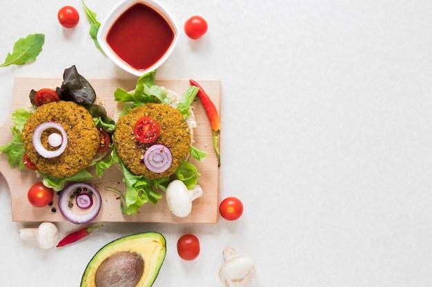 Vegane burger der flachen lage auf hölzernem brett mit kopienraum