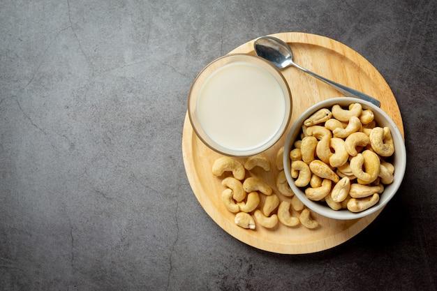 Vegane cashewmilch im glas mit cashewkernen auf dunklem hintergrund