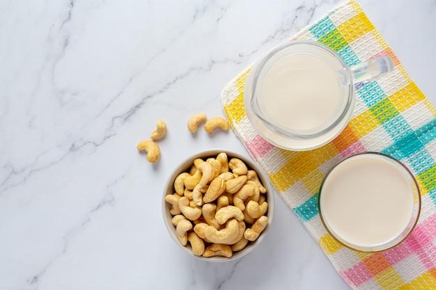 Vegane cashewmilch im glas mit cashewkernen auf marmorhintergrund