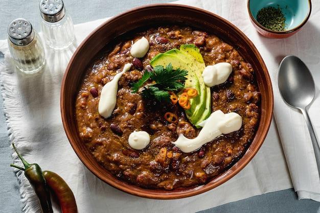 Vegane chilisuppe ohne fleisch, mit pintobohnen und avocado, serviert mit joghurt aus soja auf leinentischdecken. gesundes essen