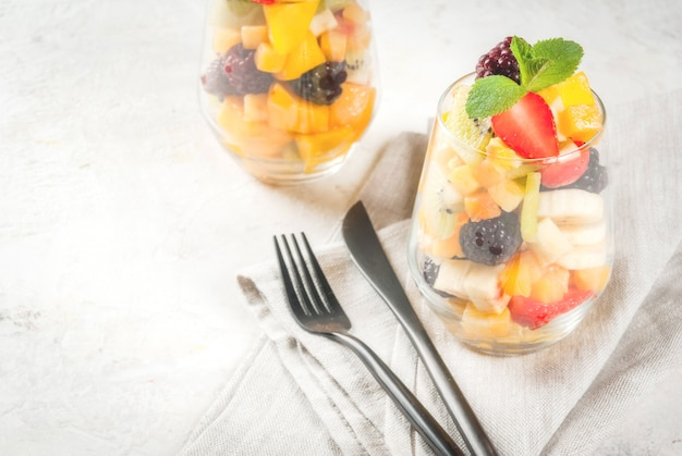 Vegane diätetische lebensmittel. vitamine. dessert. sommer. salat von frischen bio-früchten - mango, pfirsich, apfel, banane, kiwi, erdbeere, brombeeren. in einem servierglas. auf einem weißen betontisch. copyspace