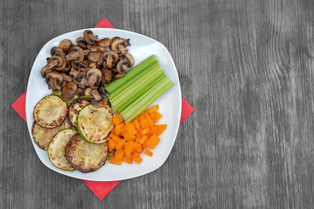 Vegane diätkost. gebratene champignons mit sellerie, karotten und zucchini.