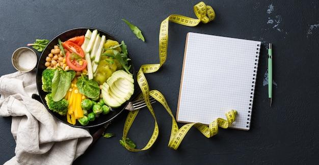 Vegane gesunde ausgewogene ernährung. vegetarische buddha-schüssel mit leerem notizbuch und maßband. kichererbsen, brokkoli, pfeffer, tomate, spinat, rucola und avocado in teller. draufsicht.