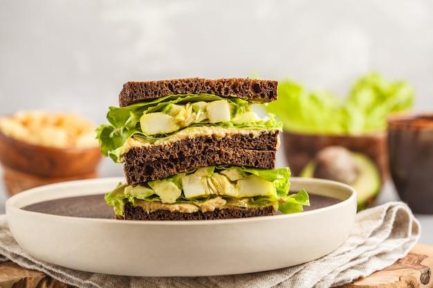Vegane grüne sandwiches mit hummus, gebackenem gemüse und avocado.