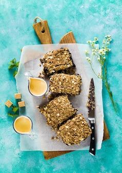 Vegane haferflocken mit blaubeeren und kokoscreme zerbröckeln. sommermorgen dessert zum frühstück mit tassen espresso