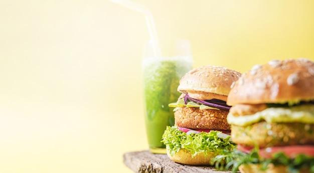 Vegane hausgemachte burger mit glutenfreiem brötchen und schnitzel auf gemüsebasis und gemüse-smoothie