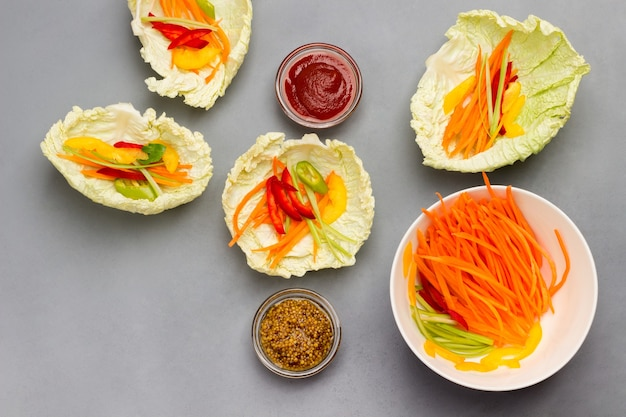 Vegane kohlblattsnacks mit karotten und senf-tomatensauce in schalen