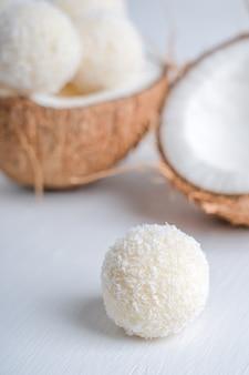 Vegane kokosnuss-trüffel mit einer quarkfüllung serviert in halber frischer kokosnuss auf einem tisch