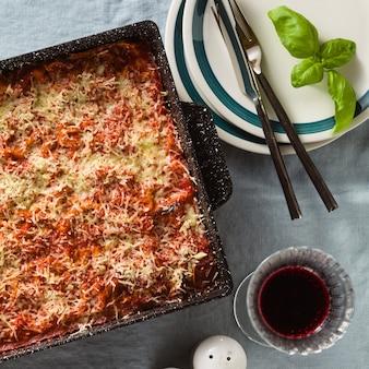 Vegane lasagne mit linsen und erbsen in einem backblech auf einem tisch mit einer blauen leinentischdecke. und rotwein in gläsern