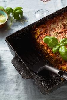 Vegane lasagne mit linsen und erbsen in einem backblech auf einem tisch mit einer blauen leinentischdecke.