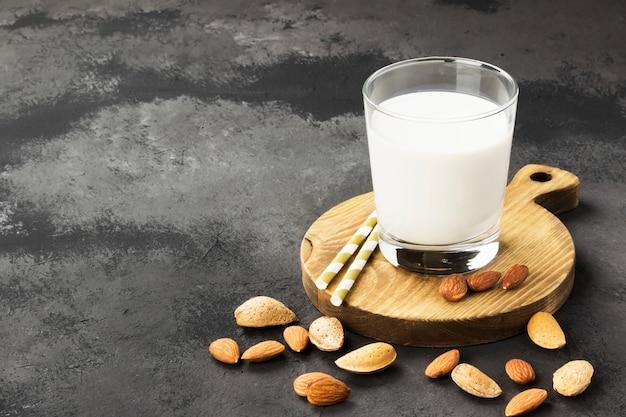 Vegane mandelmilch im glas auf einem dunklen hintergrund. milch ohne milch platz kopieren. essen hintergrund