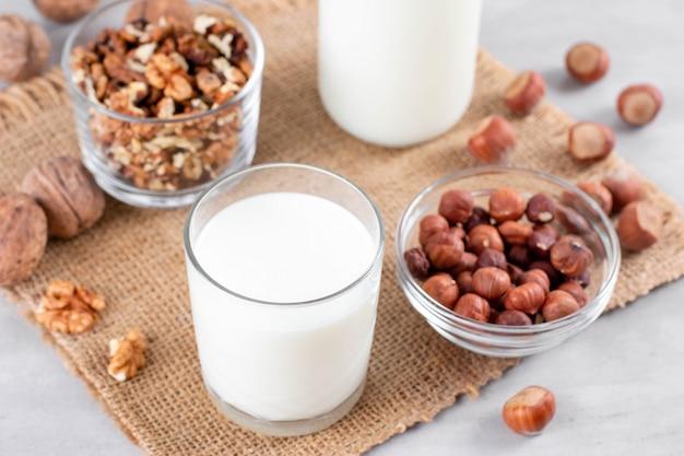 Vegane milch von nüssen im glas mit verschiedenen nüssen auf weißem hölzernem hintergrund
