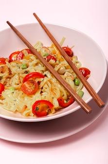 Vegane nudeln mit erbsen, paprika, zwiebeln und zucchini