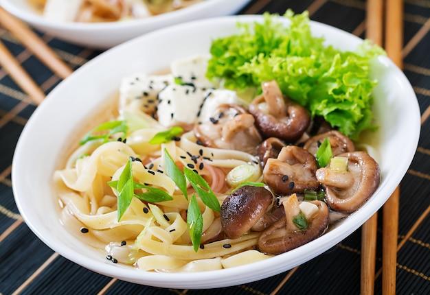 Vegane nudelsuppe mit tofu-käse, shiitake-pilzen und salat in weißer schüssel.