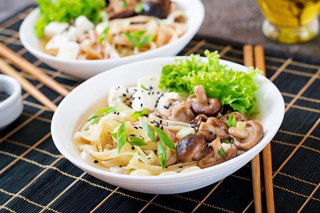 Vegane nudelsuppe mit tofukäse, shiitake-pilzen und salat in weißer schüssel. asiatisches essen.