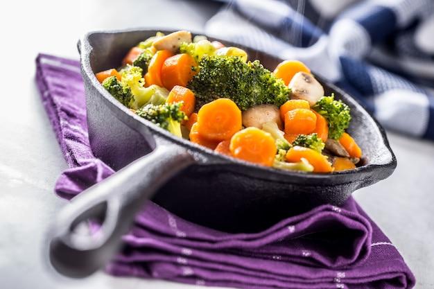Vegane pfanne. vegetarisches essen - brokkoli-karotten-pilze salzpfeffer auf butter.